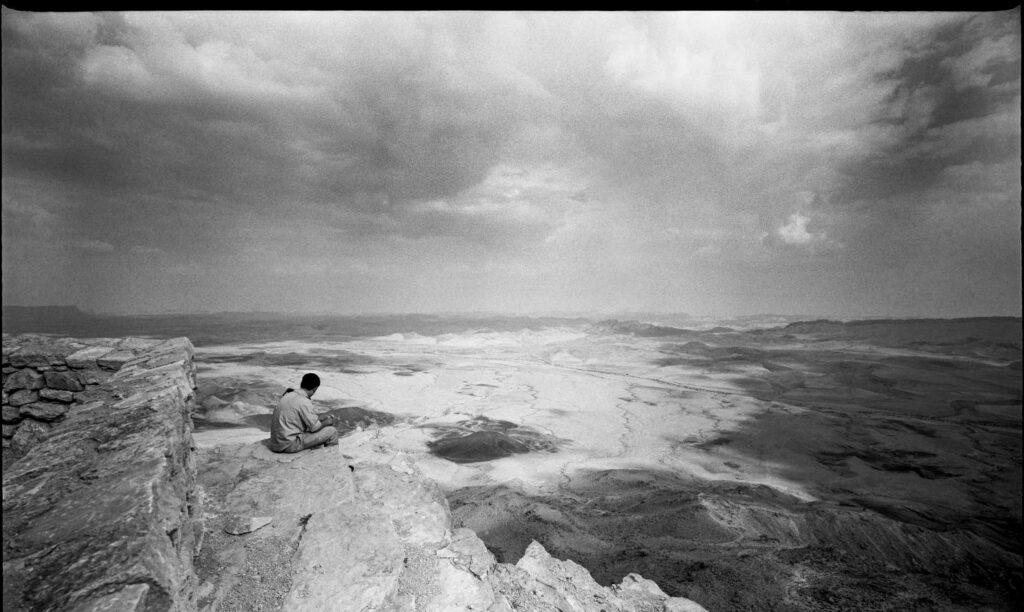 Homme assis au bord d'une falaise contemplant le paysage d'Israel