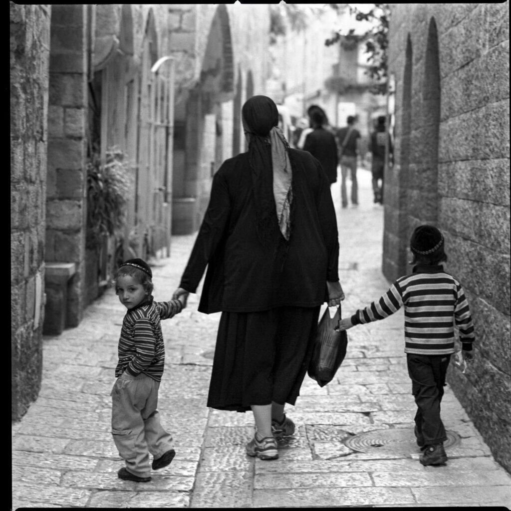Femme tenant la main de deux petits garçons dans les rues d'Israël