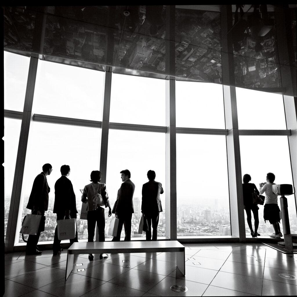 Les travailleurs tokyotes dans un immense building contemplant la vue à travers les baies vitrées