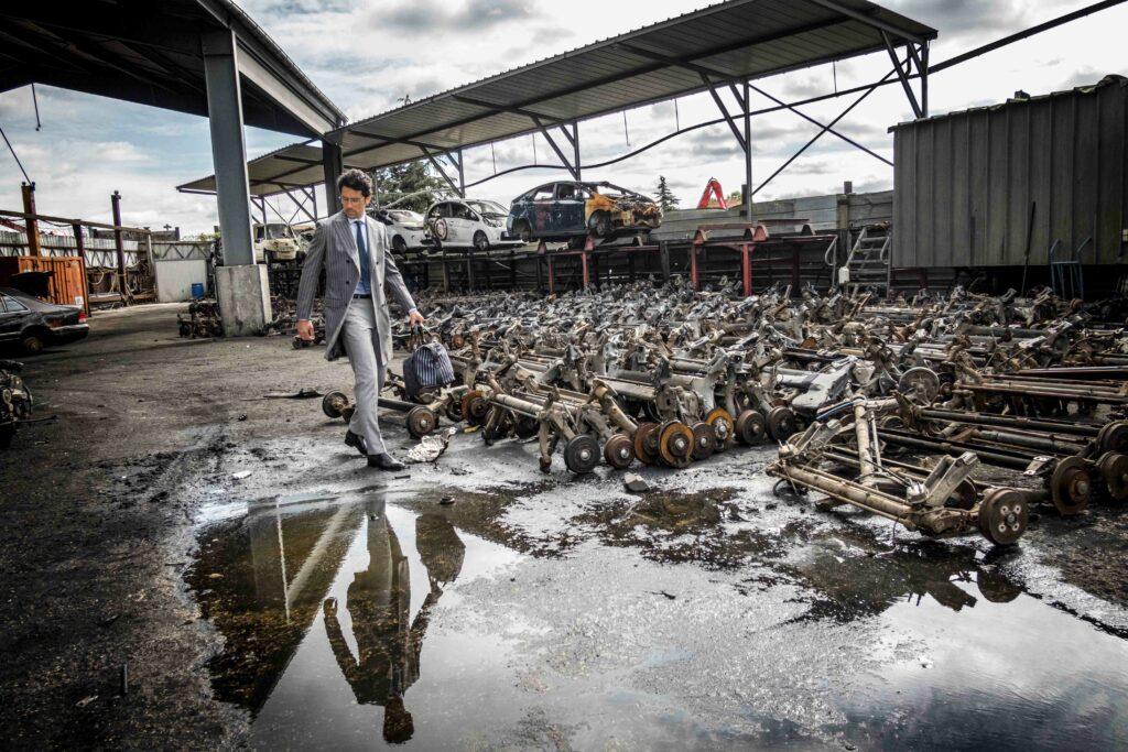 Photo de mode montrant un homme qui se trouve dans une case auto, entouré de pièces de voiture, il marche et son reflet apparaît dans une flaque d'eau en face de lui.