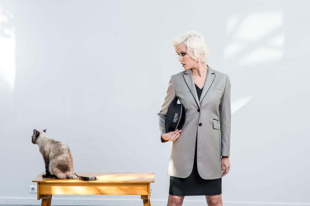 Photo de mode, on y voit une femme en costume qui observe un chat qui se trouve à ses côtés sur une table