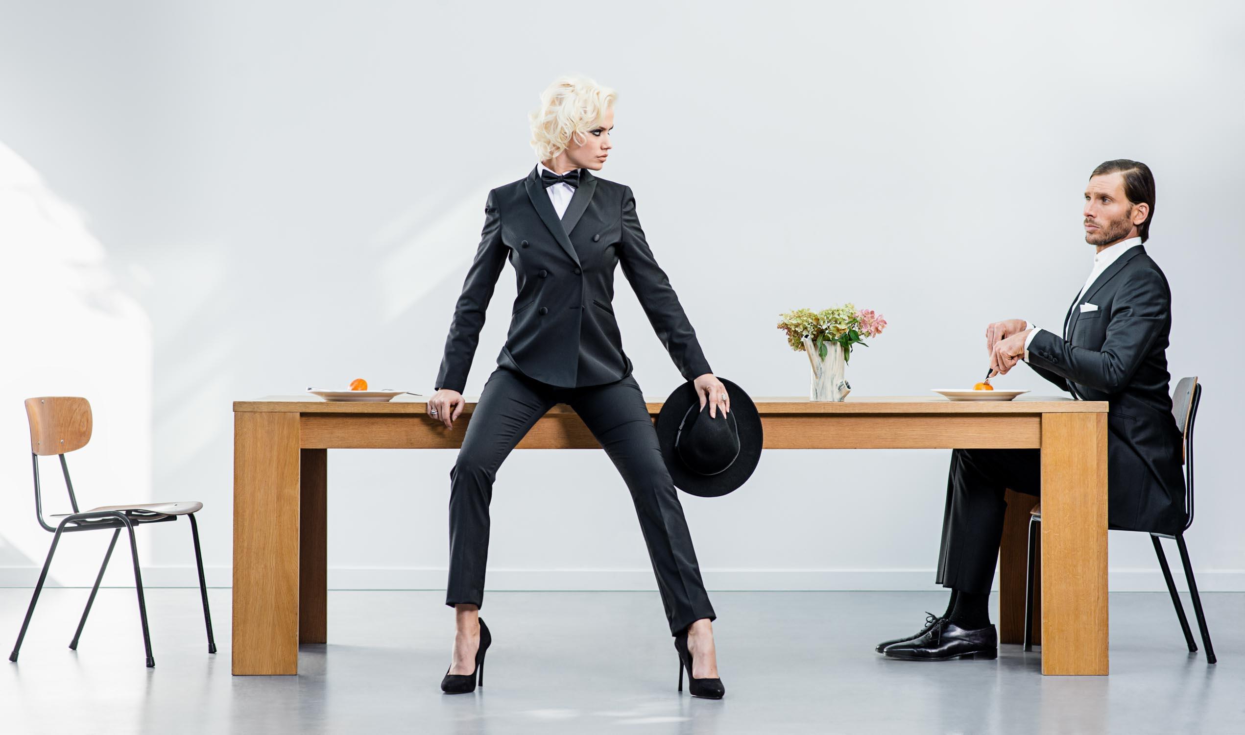 Photo de mode, femme assise sur une table qui regarde un homme qui se prépare à manger