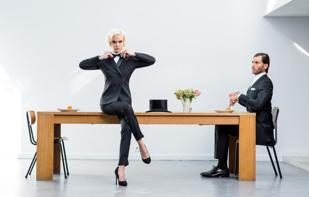 Photo de mode, femme assise sur une table et homme qui se prépare à manger