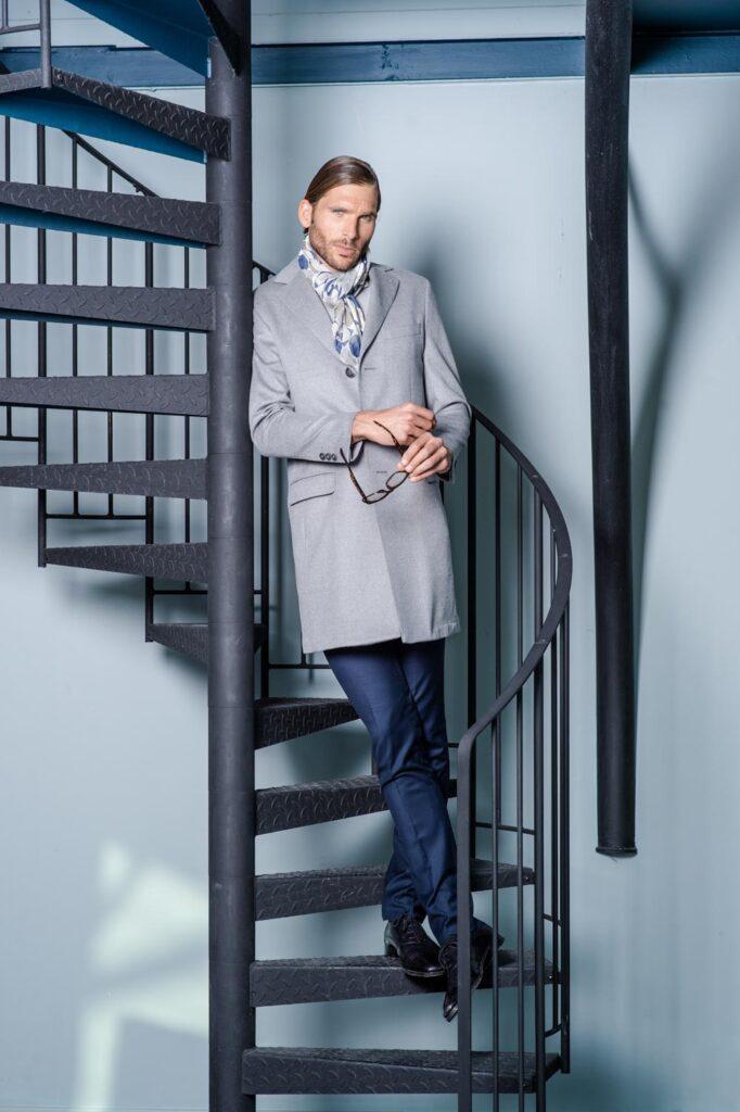 Photo de mode, on y voit un homme en costume se tenant sur des escaliers