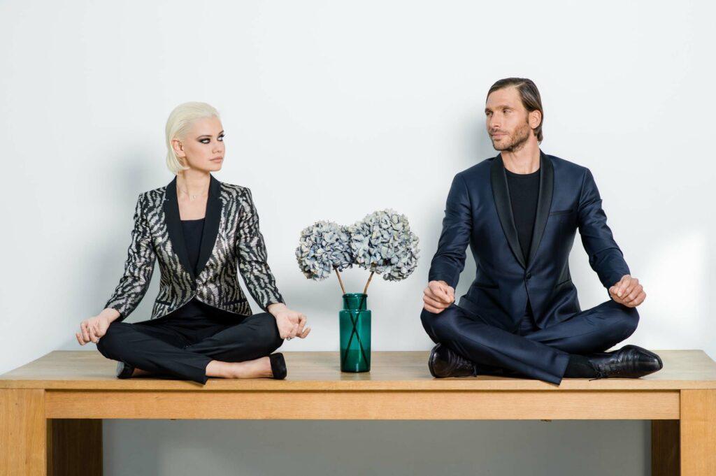 Photo de mode, on y voit un homme et une femme en tailleur sur une table