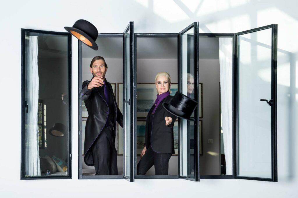 Un homme et une femme jetant leur chapeau à travers une fenêtre