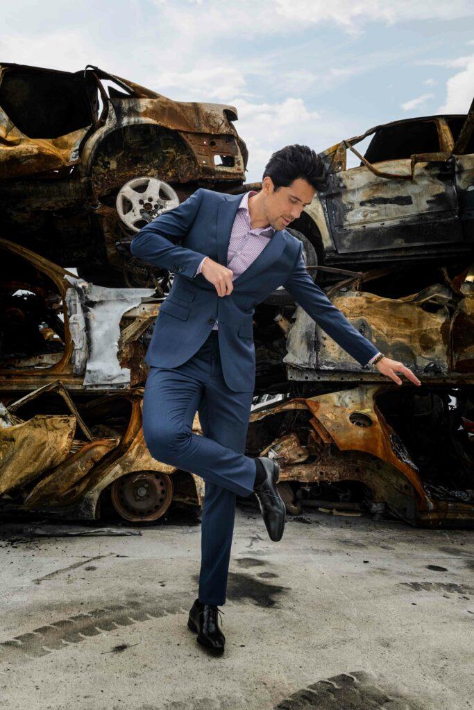 Photo de mode montrant un homme qui se trouve dans une case auto, entouré de vielles voiture