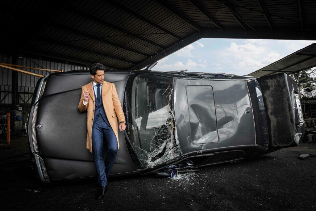Photo de mode montrant un homme adossé a une voiture ou la vitre a été brisé, il porte un beau costume de la marque The French Tailor Paris
