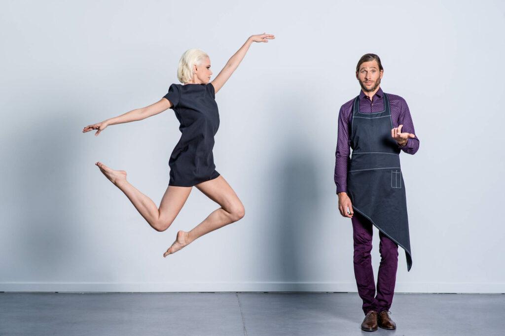 Photo de mode, Femme qui saute en figure acrobatique aux cotés d'un homme étonné
