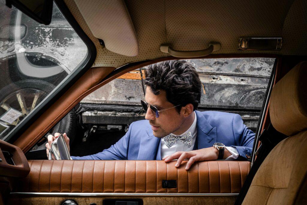 Photo de mode montrant un homme qui se regarde dans le rétro d'une voiture de case