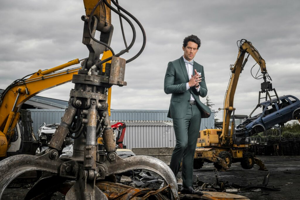 Photo de mode montrant un homme qui se trouve dans une case auto, entouré de pièces de voiture dans son costume de la marque The French Tailor Paris