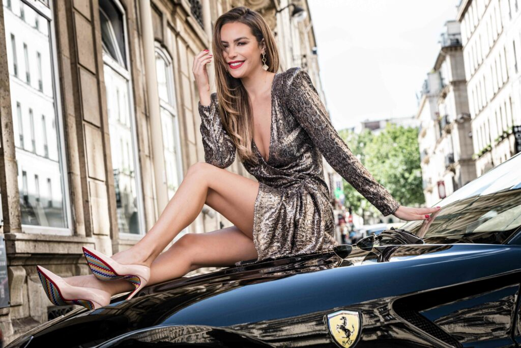 Femme assise sur une voiture de la marque Ferrari