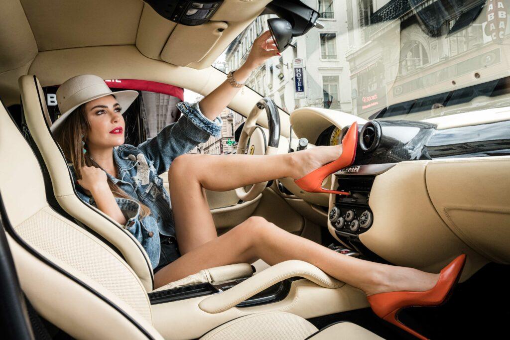 Femme assise dans une voiture de la marque Ferrari