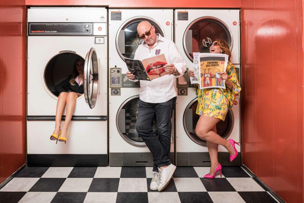 Femme assise dans une machine retro et passant qui bouquine dans une laverie parisienne