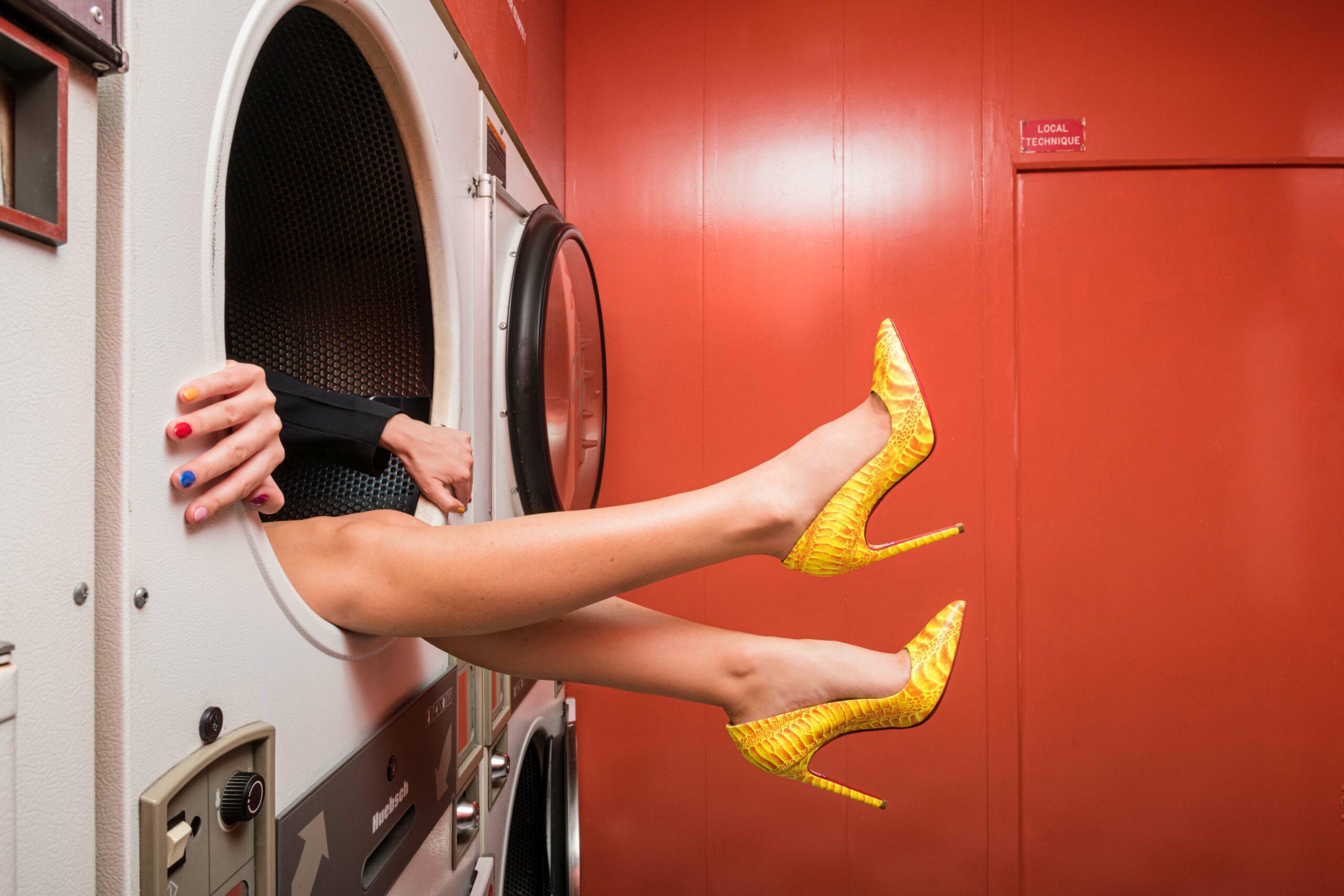 Femme dans la machine à laver d'une laverie parisienne