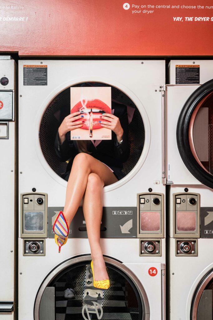 Femme assise dans une machine à laver retro