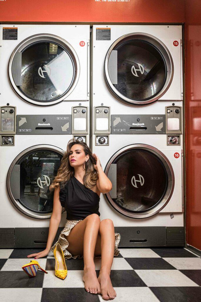 Femme en escarpins assise dans une laverie parisienne