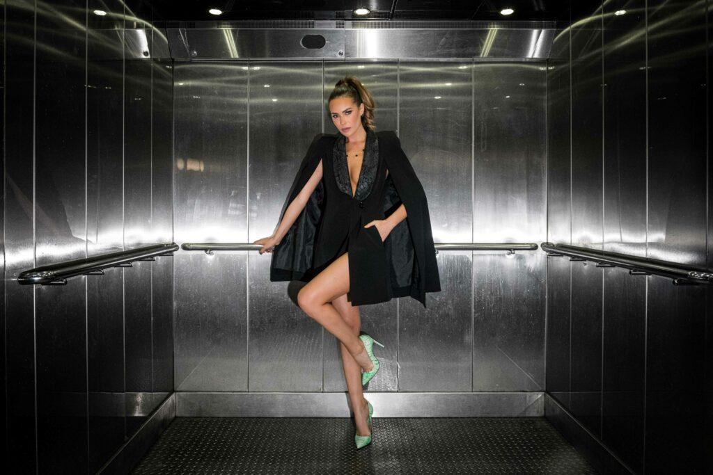 Femme en escarpins et tenu glamour dans un ascenseur parisien