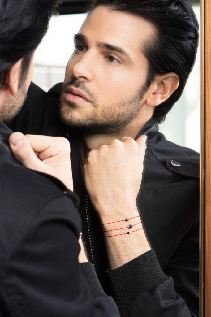 Photo en couleur, portrait homme qui se regarde dans le miroir et porte des bijoux de la marque Redline Paris