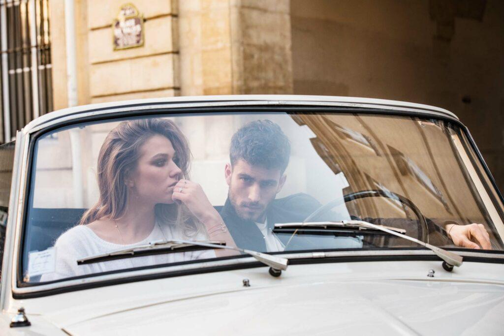 Photo en couleur, un couple dans une voiture portant des bijoux de la marque haute couture Redline Paris