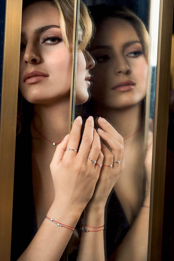 Femme qui se regarde dans un miroir, elle porte des bijoux de la marque Redline Paris