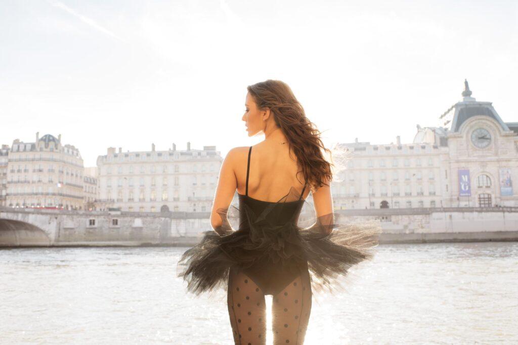 Danseuse observant la ville au bord du canal parisien