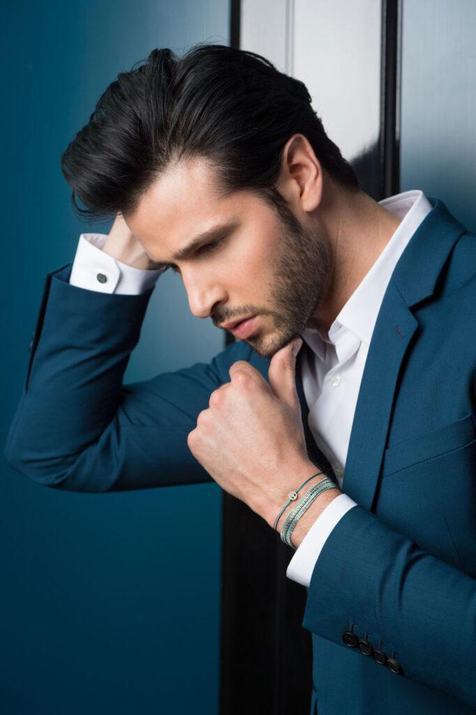 Photo en couleur, portrait homme se touchant les cheveux et porte des bijoux de la marque Redline Paris