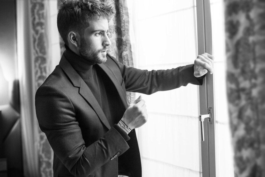 Photo en noir et blanc, homme qui regarde par la fenêtre et porte des bijoux de la marque Redline Paris