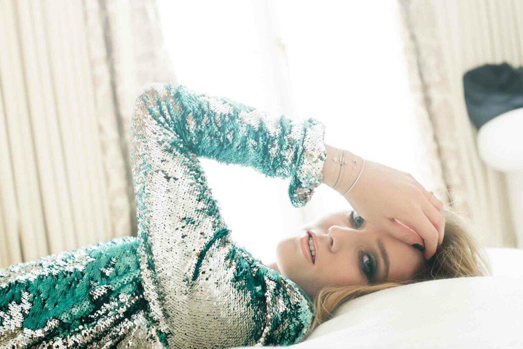 Femme allongée sur un lit portant une robe pailletté