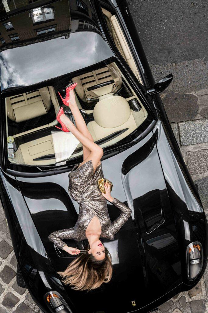 Femme allongée sur une voiture de marque Ferrari